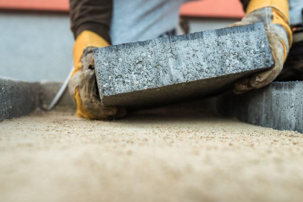 man laying heavy pavers