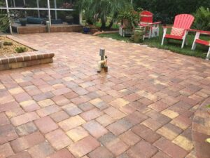 A nice paver patio with a yard and chairs around it