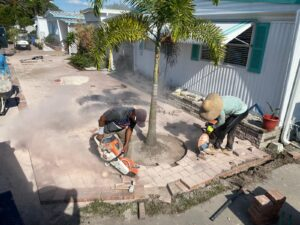 Two workers cutting pavers with mansory blades in a patio