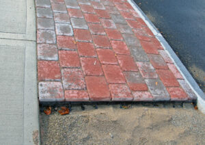 Sidewalk made with brick pavers with edge restrains installed on the perimeter
