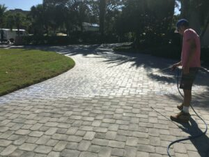 Paver patio being cleaned by a man with a pressure washer