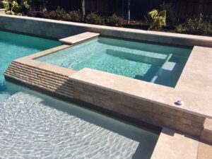 Pool area surrounded by travertine pavers.