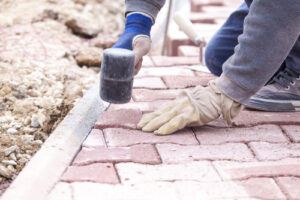 Close up of a person installing pavers with a rubber hammer.